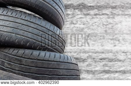 Old Unnecessary Car Tires On A Concrete Background. Worn Wheel Replacement Concept.