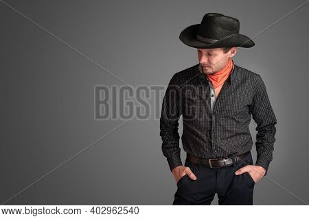 Cowboy In A Black Shirt With His Hands In His Pants Pockets. Unshaven Smiling Man In A Hat. Macho Gu