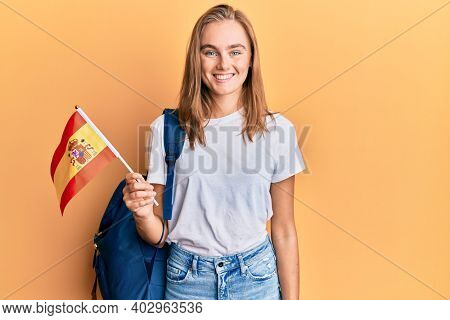 Beautiful blonde woman exchange student holding spanish flag looking positive and happy standing and smiling with a confident smile showing teeth