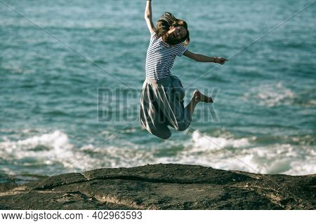A young dance woman is engaged in choreography on ocean coast.