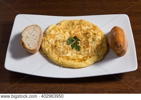Piece Of Omelet With Eggs And Potatoes On White Plate. Spanish Omelette - Traditional Tortilla Tapas