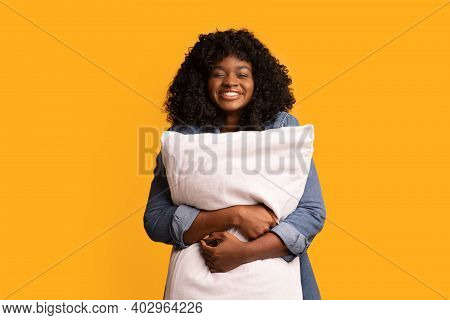 Playful Young Black Woman Hugging Big Soft Pillow Over Yellow Studio Background, Copy Space. Smiling