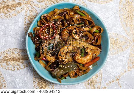 Buckwheat Stir-fry Noodles With Seafood - Shrimps, Octopus, Squid In Cast Iron Asian Wok With Cookin