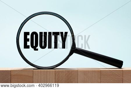 Cubes On A Light Blue Wooden Background. On Them A Magnifying Glass With The Word Equity.