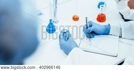 Close Up. A Scientist Writing Down The Formula For A New Drug .
