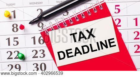 On The Calendar Is A White Card With The Text Tax Deadline. Nearby Is A Red Notepad And A Marker. Vi
