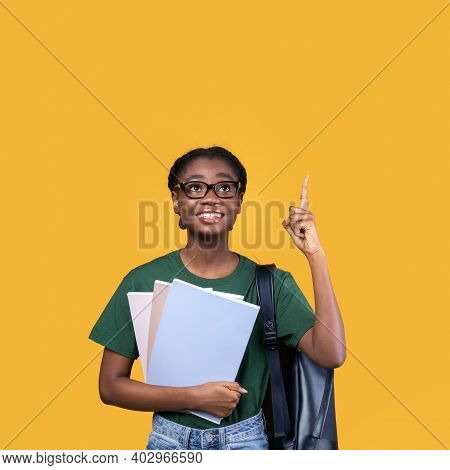 Look Up. Happy African Student Woman Pointing Finger Up Having Great Idea Standing Holding Books On