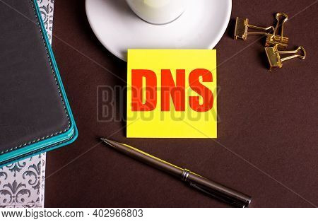 The Word Dns Written On Yellow Paper On A Brown Background Near A Coffee Cup And Diaries.