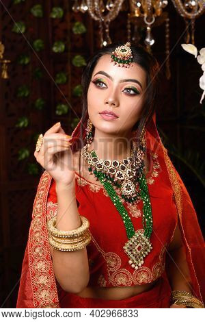 Close Up Portrait Of Very Beautiful Young Indian Bride In Luxurious Bridal Costume With Makeup And H