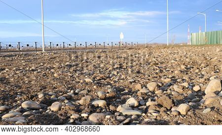 Excavated Land Of The Urban Area On The Outskirts Of The City With A Fence And Lanterns In The Dista