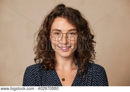 Young woman wearing eyeglasses isolated on beige background and looking at camera. Proud female student with nerd glasses isolated on wall. Sophisticated glamour girl in shirt wearing big spectacles.
