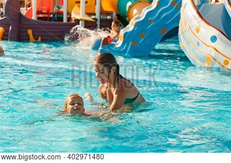 A Beautiful Older Sister Helps Her Little Younger Sister Learn To Swim In A Pool With Clear And Tran