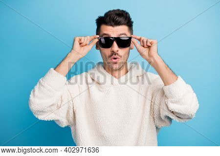 Photo Portrait Of Chill Guy With Stubble Touching Glasses With Two Hands Isolated On Pastel Blue Col