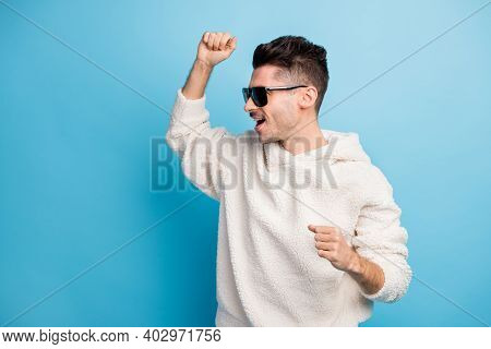 Photo Portrait Of Cheerful Man With Stubble Dancing Isolated On Pastel Blue Colored Background