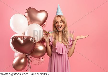 Young Blonde Lady With Festive Balloons, Birthday Cap And Party Blower Celebrating Special Occasion