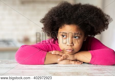 Portrait Of Cute Sad Little Black Girl Sitting At Table In Kitchen. Lonely African American Female K