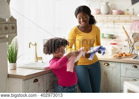 Cute African American Girl Helping Mother With Household, Wiping Dishes In Kitchen After Washing. Ad