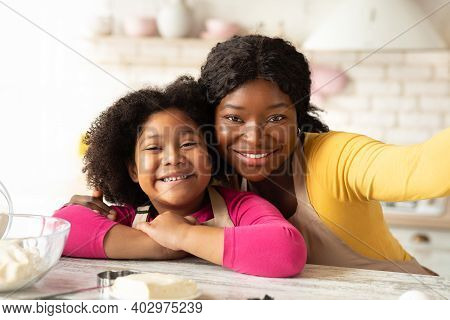 Happy African Mom Taking Selfie With Her Little Daughter In Kitchen. Cheerful Black Mother And Child