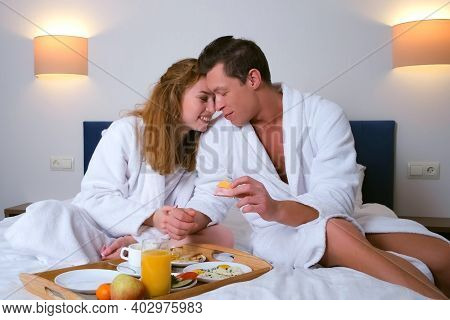 Family On Vacations Resting In Their Room. Happy Young Couple In Bathrobes Having A Breakfast Togeth