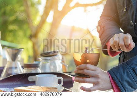 Asian Women Hands On Manual Grinder Coffee For Grinding Coffee Beans On Table With Natural Green Bac