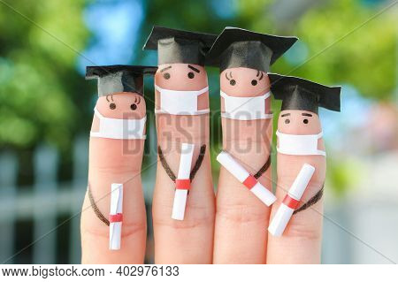 Fingers Art Of Students In Medical Mask From Covid-2019. Graduates Holding Their Diploma After Gradu