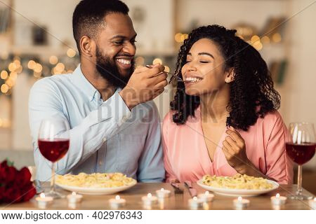 Romantic Date Concept. Smiling African American Guy Feeding His Cute Girlfriend With Pasta. Portrait