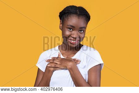 Gratitude. Thankful Black Young Lady Pressing Hands To Chest Posing Smiling To Camera Standing Over