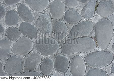 Background From Large Gray Cobblestones. The Old Cobbled Road. Close-up. View From Above.