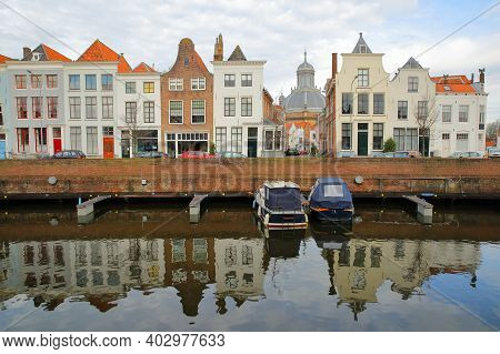 Reflections Of Colorful Facades Along Dam Street In Middelburg, Zeeland, Netherlands, With The Octag