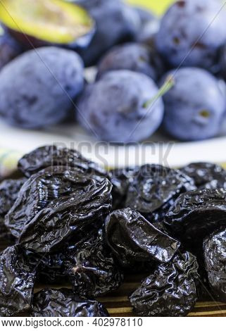 Dried Plum In The Foreground Plum On A White Plate Background Blurred Background Top View Red Backgr