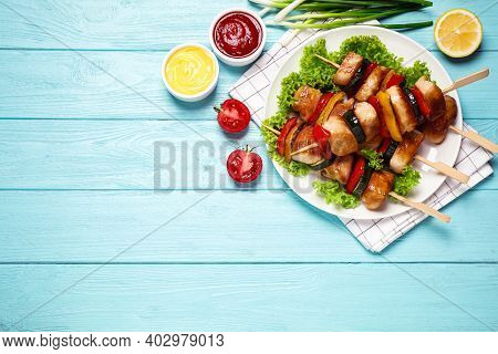 Delicious Chicken Shish Kebabs With Vegetables And Sauce On Light Blue Wooden Table, Flat Lay. Space