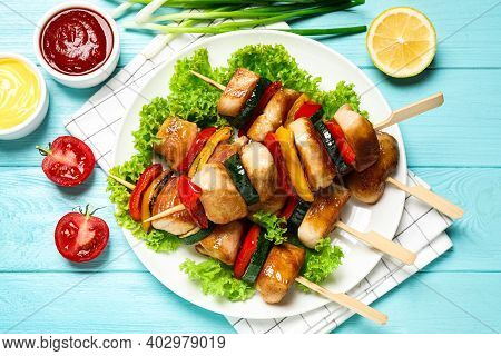 Delicious Chicken Shish Kebabs With Vegetables And Sauce On Light Blue Wooden Table, Flat Lay