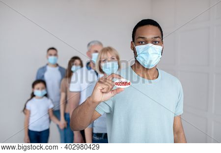 African American Guy In Face Mask Showing Vaccinated Badge, Standing In Queue At Clinic, Waiting For