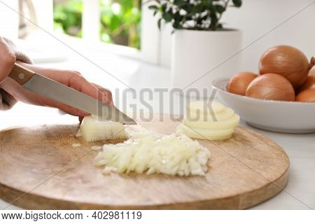 Woman Chopping White Onion On Wooden Board At Table, Closeup