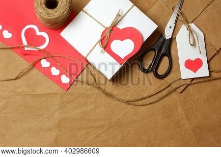 Gifts Wrapped In Brown Craft Paper, Tied With Twine With Bows And Labels, String, Scissors, Coil Of