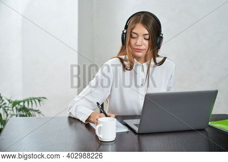 Beautiful Young Woman In Modern Headphones Taking Notes While Studying On Laptop. Distance Learning