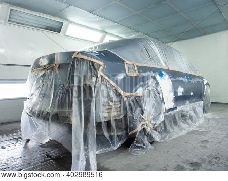 Car Prepared For Painting In A Spray Booth. Car Putty Applied To Car Parts.