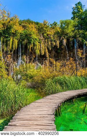 Travel to Central Europe. Plitvice Lakes Park in Croatia. Wooden footbridge over a picturesque shallow lake. Plitvice Lakes are beautiful karst lakes of turquoise color.