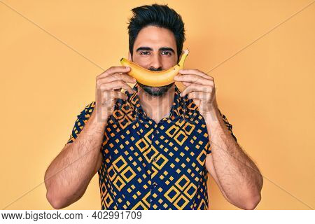 Handsome hispanic man with beard holding banana like funny smile smiling with a happy and cool smile on face. showing teeth.