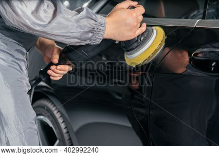 Worker Polishing Car With Special Grinder And Wax From Scratches At The Car Service Station. Profess