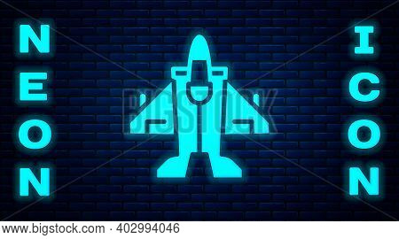 Glowing Neon Jet Fighter Icon Isolated On Brick Wall Background. Military Aircraft. Vector