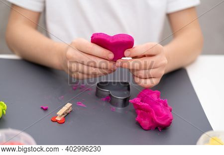 A Girl In A White T-shirt Sculpts A Pink Heart From Plasticine. Valentine's Day, Mother's Day, Fathe