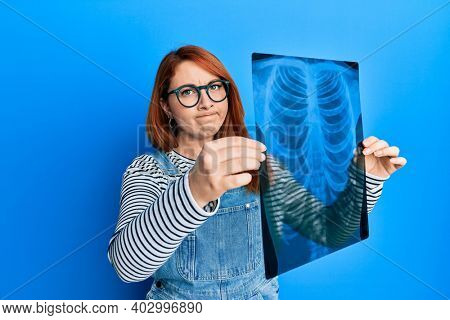 Beautiful redhead woman holding chest radiography skeptic and nervous, frowning upset because of problem. negative person.
