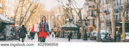 Happy Asian woman walking on La Rambla city street with shopping bags from open stores outside. Urban background panoramic.