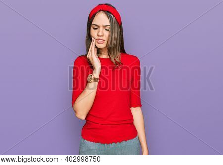 Young brunette woman wearing casual clothes touching mouth with hand with painful expression because of toothache or dental illness on teeth. dentist