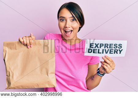 Beautiful young woman with short hair holding paper pag with express delivery text afraid and shocked with surprise and amazed expression, fear and excited face.