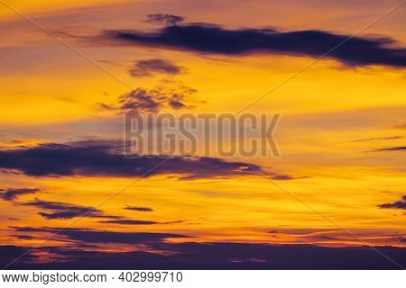 Dark Clouds On The Glowing Sky At Sunset. Dramatic Nature Scenery On The Windy Weather In Evening