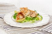 Healthy eating. Grilled fish fillet with fresh rocket salad lettuce and avocado on white plate on white wooden textured background. poster