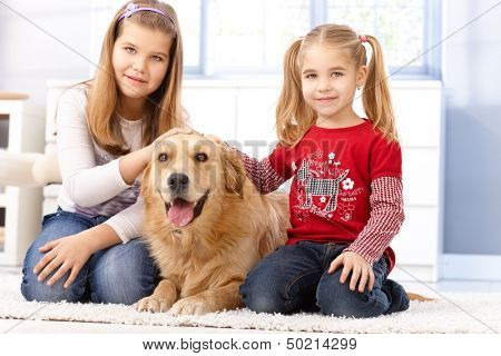 Little sisters kneeling on floor at home, fondling pet golden retriever, smiling.