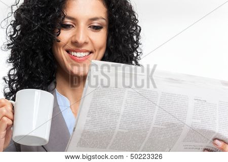 Beautiful woman reading a newspaper while drinking coffee